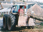 A blue tractor with four equally sized wheels and very heavy armouring pulls a huge tree stem from amongst thick foilage