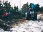 A large red wood chipper being operated next to the Blue Tractor with a workman inbetween the two large machines, and another fe