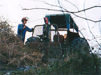 The blue old fasioned tractor using the winch facility pulls a heavy tree up from a very steep banking