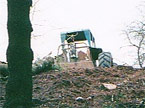 The tractor at the top of a steep banking pulls the heavy tree stem over the virge at the top of the incline