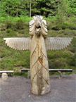 Front view of a massive totem pole which has a head a bit like an eagle, and wings