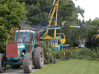 A large tractor and crane work together to clean up the site of a large tree fell