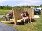 Large sleeper benches designed so that bikes can be parked around the back while the cyclists sit around the front and get some well deserved rest and relaxation